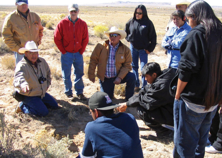 A group of ranchers in a field discussing something