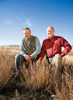 Two men kneeling next to a shrub in a Western rangeland