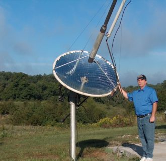 Dan West next to a solar collector