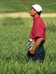 Farmer standing in a field, holding a book.