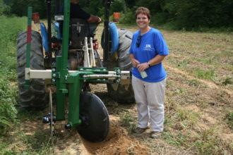 Sarah Fannin standing next to a sweet potato harvester.