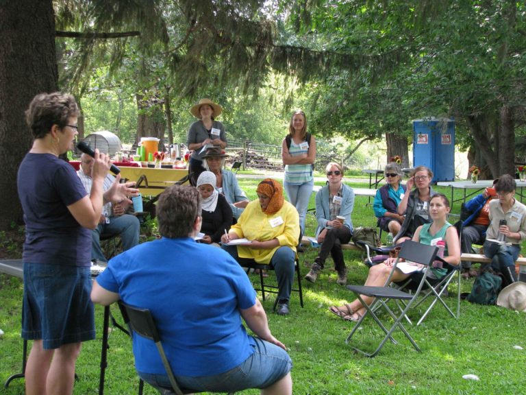 A woman speaking to women outdoors