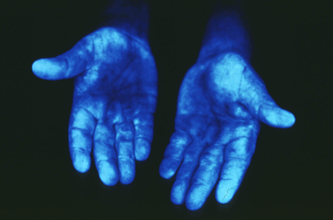 pair of hands glowing blue under special light